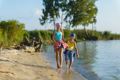 Brother and Sister run along Beach. Holiday and Travel Concept.  Royalty Free Stock Photo