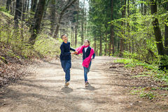 Brother and Sister running in a forest hand in hand Royalty Free Stock Image