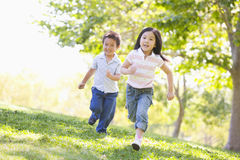 Brother and sister running outdoors smiling Stock Photo