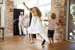 Brother and sister rush to meet their visiting grandparents royalty free stock photo