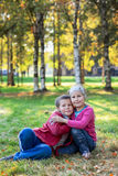 Brother and sister same age embracing in autumn park Stock Images