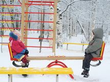 Brother and sister on seesaw. In winter park Royalty Free Stock Photos