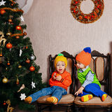 Brother and sister share an apple near Christmas tree. Royalty Free Stock Photography
