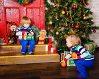 Brother and sister share gifts near Christmas tree. Royalty Free Stock Image