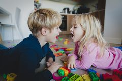 Brother and sister shout at home with toys scattered on floor, family problems stock photography