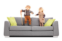 Brother and sister siblings standing and playing on a sofa Royalty Free Stock Photos