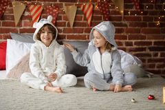 Brother with sister sit on a bed and expect Christmas gifts. Christmas holiday. Bedroom is decorated with Christmas garlands. Brother and sister of younger Royalty Free Stock Photography