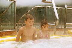 Brother and sister sit in pool with hot water Royalty Free Stock Photos