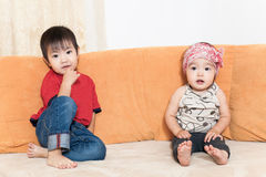 Brother and sister sit on sofa Stock Image