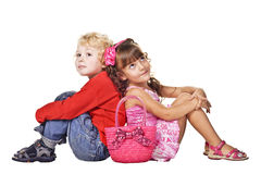Brother and sister sitting back to back. Portrait of brother and sister sitting back to back and dreaming Royalty Free Stock Photo