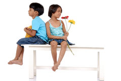 Brother and sister sitting on bench. Twins brother and sister sitting on bench with backs to each other stock photos