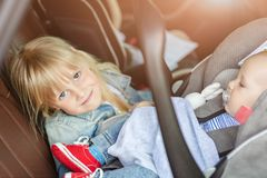 Brother and sister sitting in car in safety seat. Siblings on passenger places having fun together during travel by stock photos