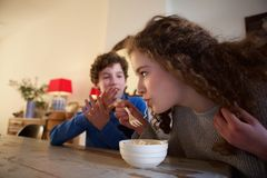 Brother and sister sitting at dining room table eating food Stock Photos