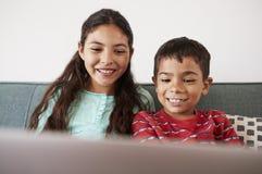 Brother And Sister Sitting en Sofa At Home Having Fun que juega en el ordenador portátil junto imagen de archivo
