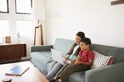 Brother And Sister Sitting en Sofa At Home Having Fun que juega en el ordenador portátil junto imágenes de archivo libres de regalías