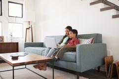 Brother And Sister Sitting en Sofa At Home Having Fun que juega en el ordenador portátil junto fotos de archivo