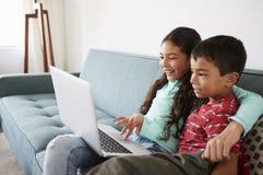 Brother And Sister Sitting en Sofa At Home Having Fun que juega en el ordenador portátil junto fotografía de archivo libre de regalías