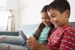 Brother And Sister Sitting en Sofa At Home Having Fun que juega en la tableta de Digitaces junto foto de archivo libre de regalías