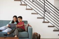 Brother And Sister Sitting en Sofa At Home Having Fun que juega en la tableta de Digitaces junto fotografía de archivo