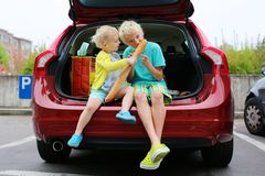 Brother and sister sitting in family car stock image