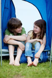 Brother And Sister Sitting In Front Of A Tent Stock Images