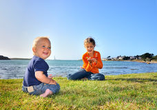 Brother and sister sitting on the grass Stock Image