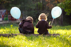Brother and sister sitting in the grass  holding blue balloons Stock Photos
