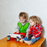Brother and sister sitting on kitchen table with tablet PC and p stock photography