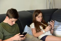 Siblings playing on their smartphone Royalty Free Stock Photos