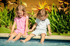 Brother and sister sitting near swimming pool Stock Photos