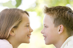 Brother and sister sitting outdoors Stock Images