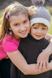 Brother and sister sitting outdoors smiling Royalty Free Stock Images