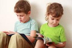 Brother and sister sitting and read books