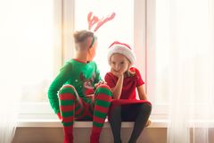 Brother and sister sitting restless on window sill at christmas time, looking out the window, anxiously waiting for Santa Claus. Brother and sister sitting royalty free stock photography