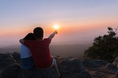 Brother and sister sitting on rock and see sunset together. At sunset view point background at Phu Hin Rong Kla National Park Phitsanulok Province, Thailand stock images
