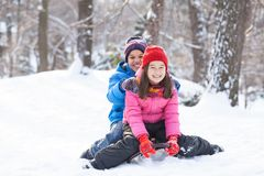 Brother and sister sitting on sledges in park. Two children sliding from hill in park Royalty Free Stock Photo