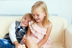 Brother and sister are sitting on the sofa Stock Image