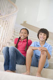 Brother And Sister Sitting On A Stairwell At Home Royalty Free Stock Photos