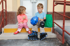 Brother and sister sitting on steps of house. Royalty Free Stock Image