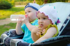 Brother and sister are sitting in a stroller. Twins stock photo