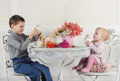 Brother and sister sitting at table with tea and decorations. Studio Royalty Free Stock Photo