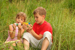 Brother and sister sitting in tall grass and play Stock Images