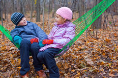 Brother and sister sitting together in a hammock Royalty Free Stock Images
