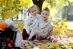 Brother and sister sitting under autumn tree Stock Image