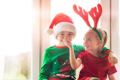 Brother and sister sitting on window sill at christmas time, having fun together. Christmas family time lifestyle. royalty free stock photos