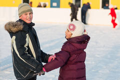 Brother and sister skating on rink hand in hand Stock Image