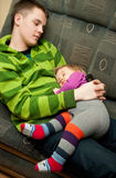Brother and sister sleep. Cute family scene - teenage brother holding a baby sister, both are sleeping on a sofa Royalty Free Stock Image