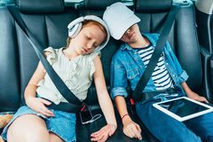 Brother and sister sleeping on backseats of car while. Having trip royalty free stock photos