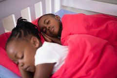 Brother and sister sleeping on bed at home stock images