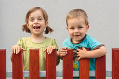 Brother and sister smiling behind the fence Royalty Free Stock Photo